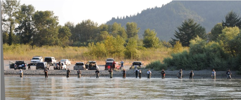 A line of anglers fish for salmon and steelhead in a riffle near Klamath Glen